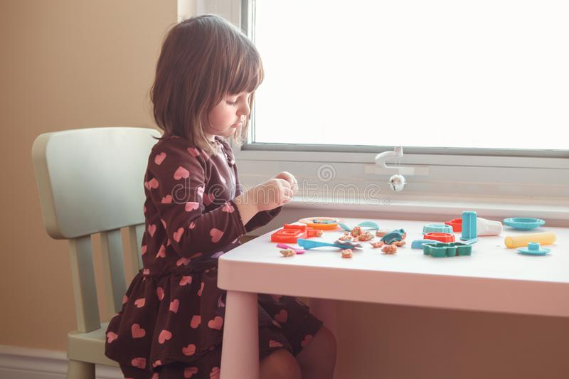 White Caucasian preschooler girl playing plasticine playdough indoors at home royalty free stock photography
