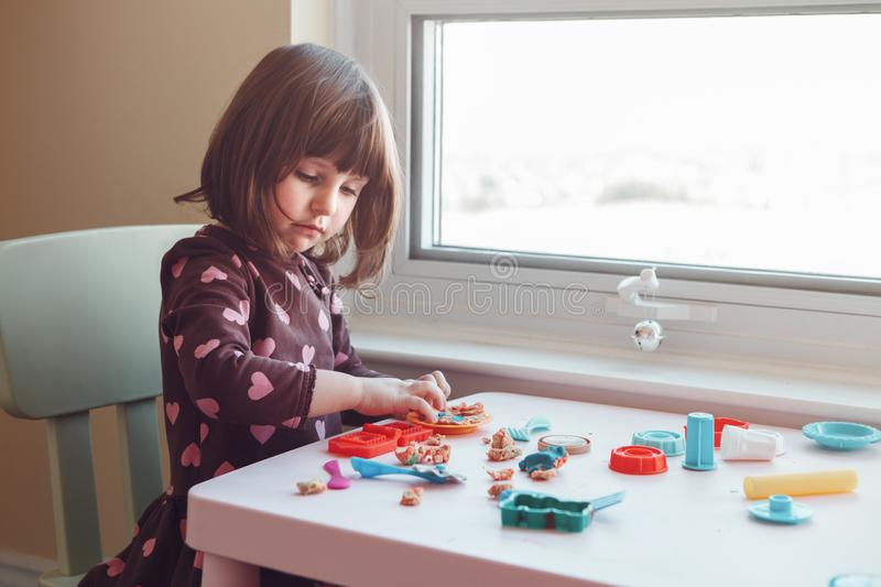 White Caucasian preschooler girl playing plasticine playdough indoors at home. Portrait of cute white Caucasian preschooler girl playing plasticine playdough royalty free stock images