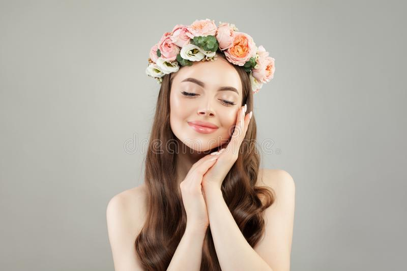 Portrait of cute woman. Beautiful model with clear skin, long hair and flowers. Relaxation, aromatherapy royalty free stock photo