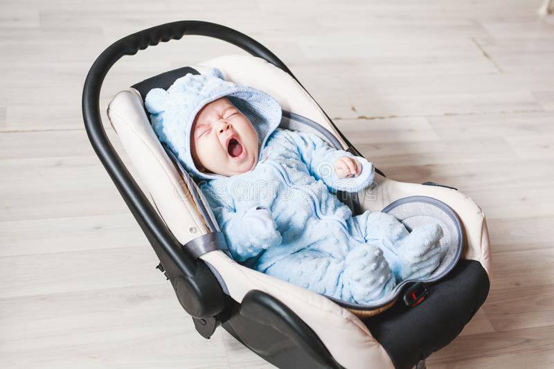 Portrait of cute yawning mixed race baby boy sitting in car seat. Child transportation safety stock photo
