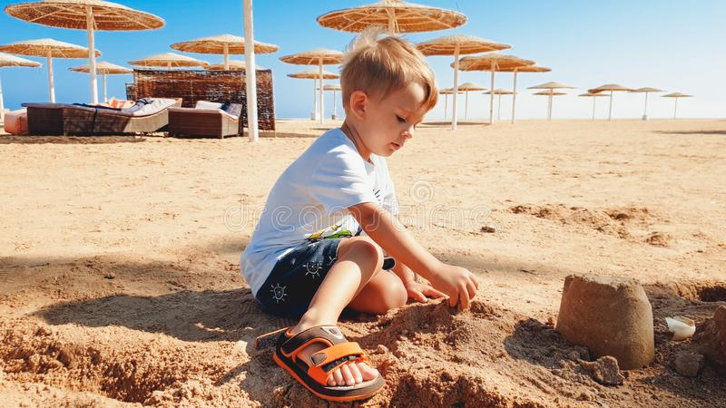 Portrait of cute 3 years old toddler boy sitting on the sandy beach and playing with toys and building sand castle stock image