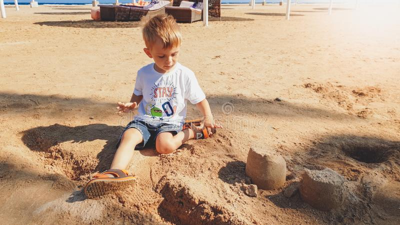Portrait of cute 3 years old toddler boy sitting on the sandy beach and playing with toys and building sand castle royalty free stock image