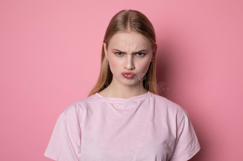 Portrait of cute young blonde girl looking angry at camera, having doubtful and indecisive face expression royalty free stock image
