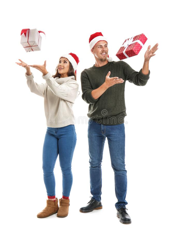 Portrait of cute young couple catching Christmas presents on white background stock photo
