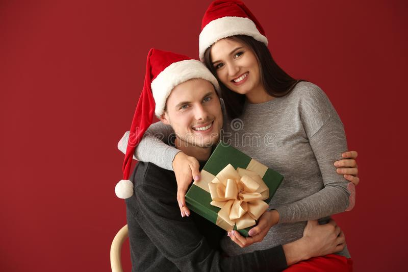 Portrait of cute young couple with Christmas gift  on color background royalty free stock photography