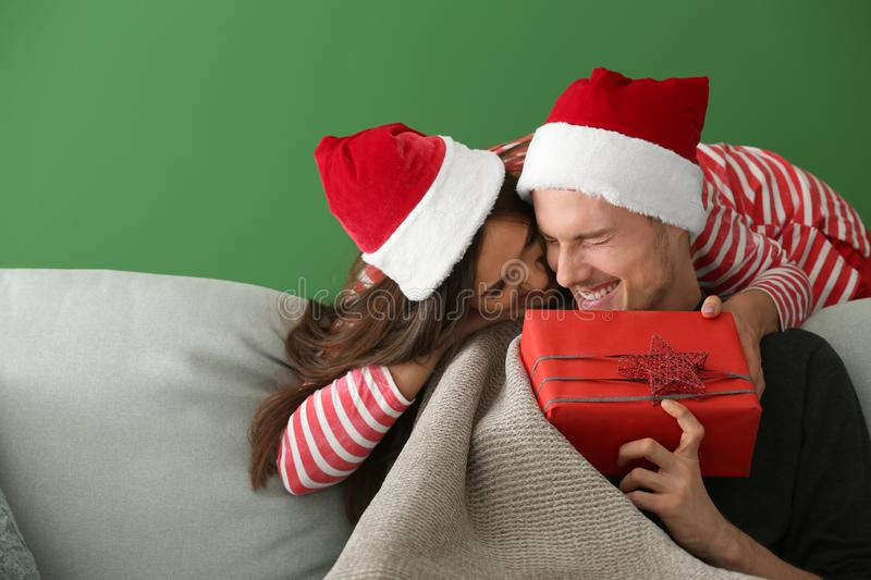 Portrait of cute young couple with Christmas gift  on color background stock photo