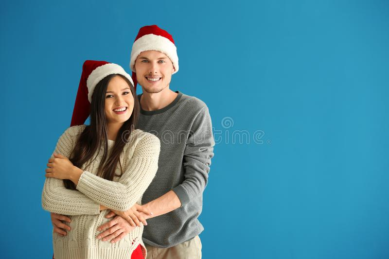 Portrait of cute young couple in Santa hats on color background stock photos