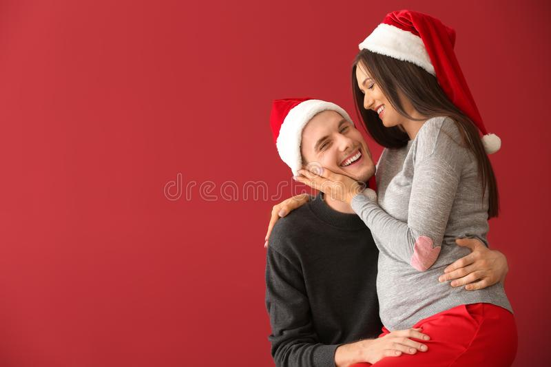 Portrait of cute young couple in Santa hats on color background royalty free stock photography