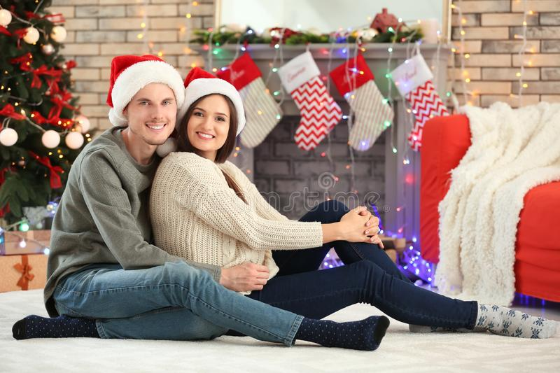 Portrait of cute young couple in Santa hats at home on Christmas eve stock photos