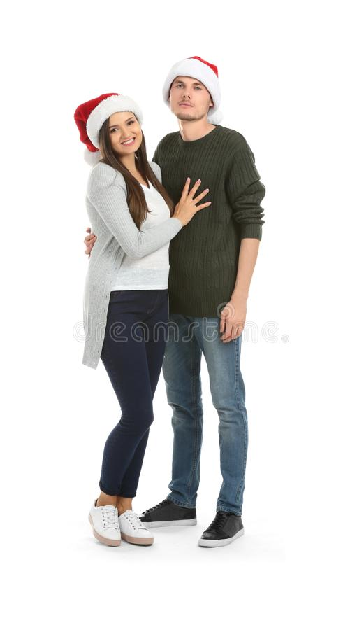 Portrait of cute young couple in Santa hats on white background stock photo
