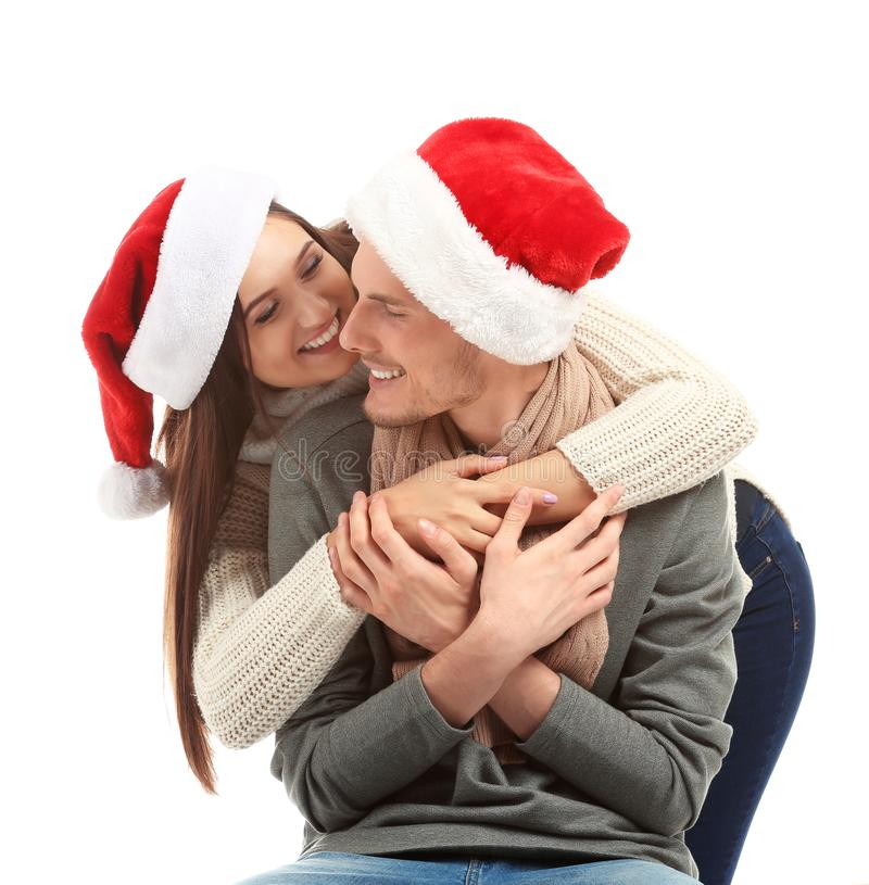 Portrait of cute young couple in Santa hats on white background stock photos