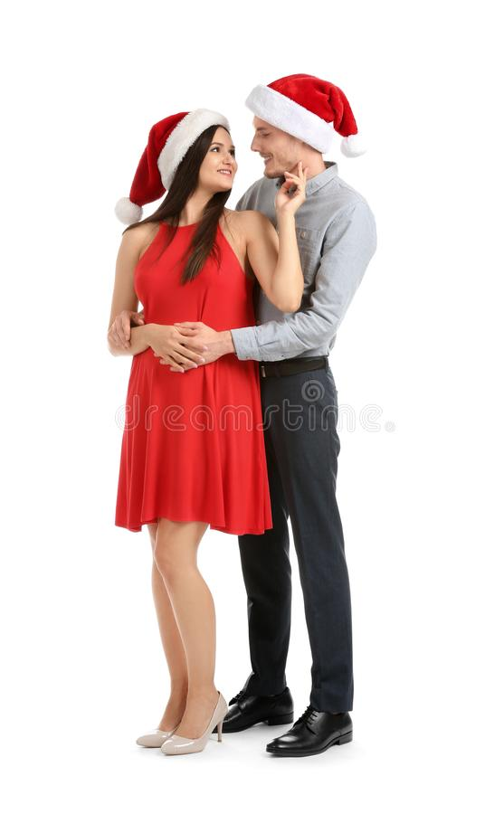 Portrait of cute young couple in Santa hats on white background stock images