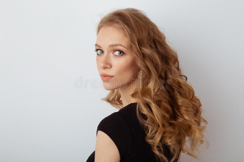 Portrait of cute young curly hair woman in the black dress posing in the white studio. stock images