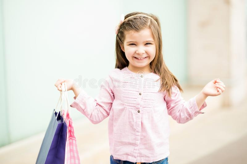 Cute young girl with shopping bags outside a mall stock image