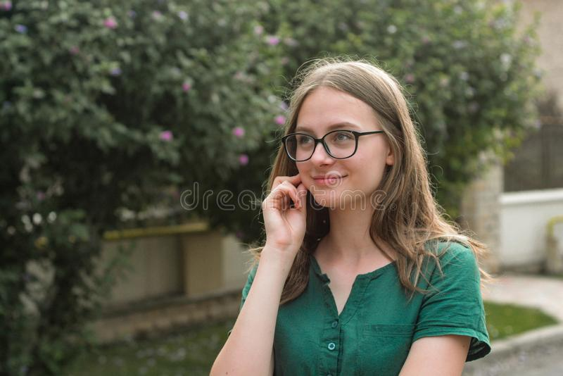 Portrait of cute young girl with eyeglasses, smiling. Blonde hair, natural, beautiful teen age girl. Summer portrait. Copy space royalty free stock images