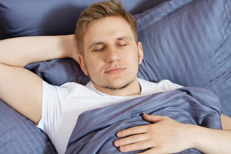 Portrait cute young man sleeping on bed bedroom stock photos