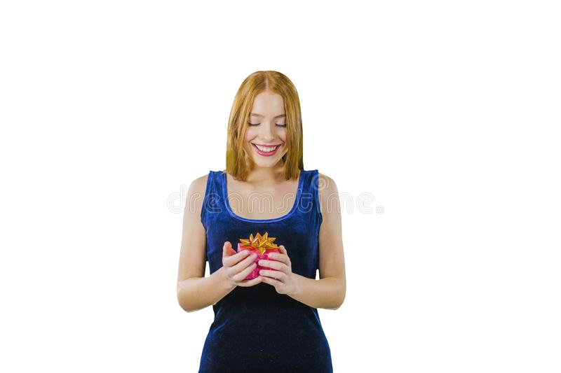 Portrait of a cute young red-haired girl in an evening dress with a box in her hands emotionally joyfully smiles as she royalty free stock photography