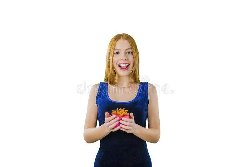 Portrait of a cute young red-haired girl in an evening dress with a box in her hands emotionally smiling and looking at stock photography