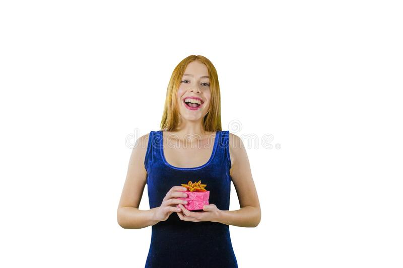 Portrait of a cute young red-haired girl in an evening dress with a box in her hands emotionally smiling and looking at stock photo