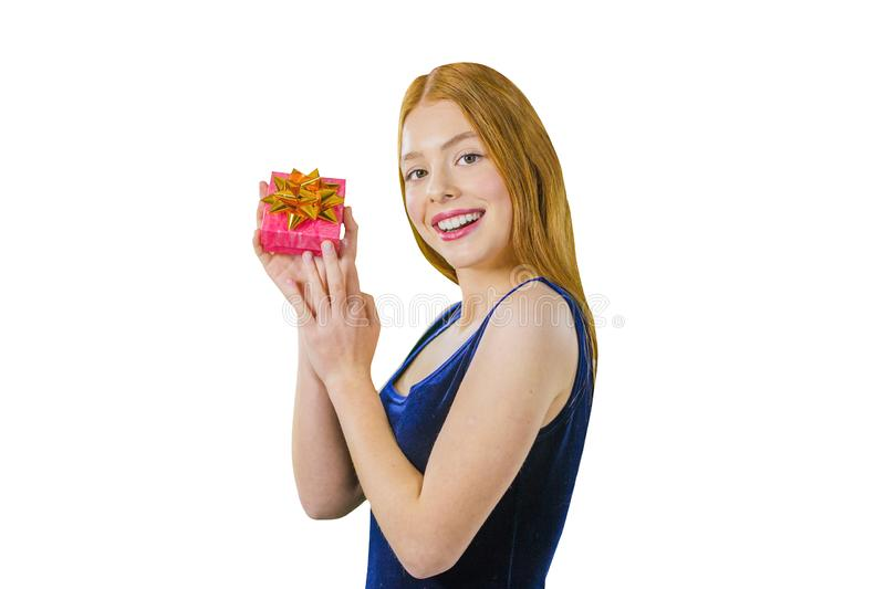 Portrait of a cute young red-haired girl who stands half a turn and holds a small box with a gift near her face, holding royalty free stock image