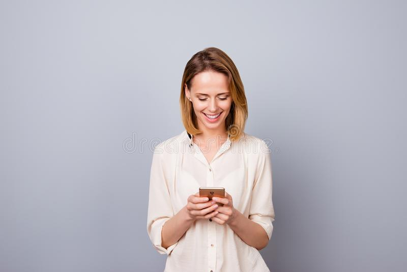 Portrait of cute young smiling woman using smartphone for messaging stock images