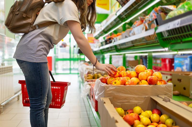 Portrait of a cute young woman with a basket in her hands, who chooses apples in the supermarket stock image