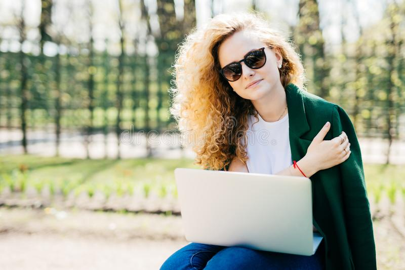 Portrait of cute young woman with curly blonde hair wearing sunglasses, white T-shirt and green jacket holding laptop on knees wor stock photography