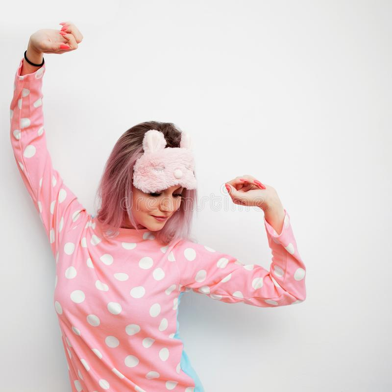 Portrait of cute young woman in pajamas and sleep mask, stretches. Woke up in the morning royalty free stock images