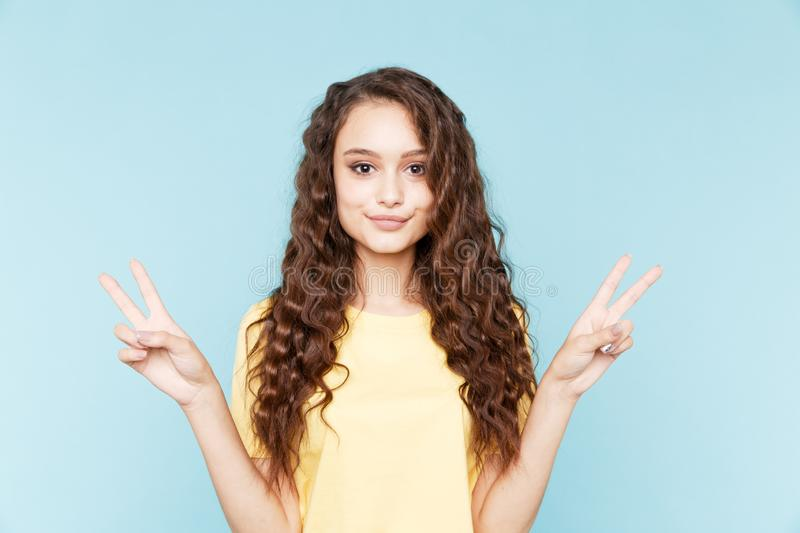 Portrait of cute young woman with peace sign isolated on the blue background. stock photography