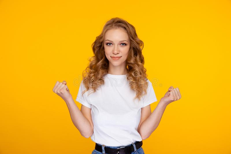 Portrait of cute young woman posing in the yellow studio. royalty free stock photo