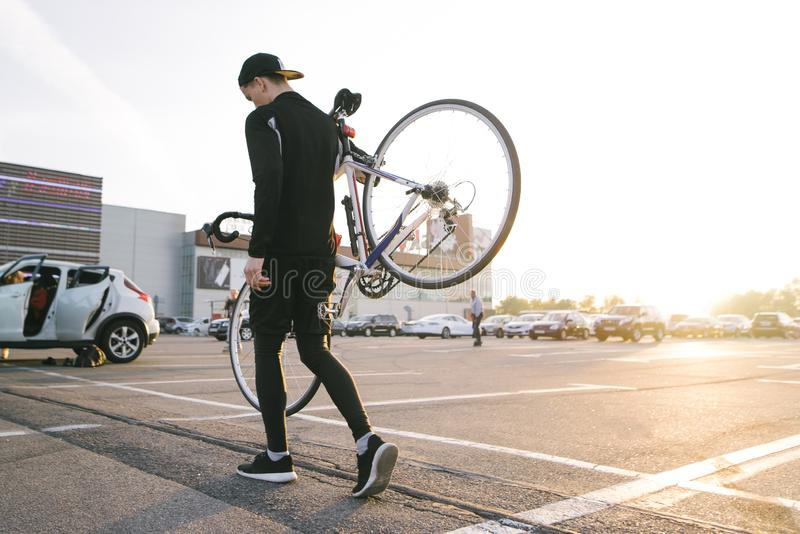 Portrait of a cyclist`s back carrying a bicycle on the background of parking at sunset royalty free stock photo