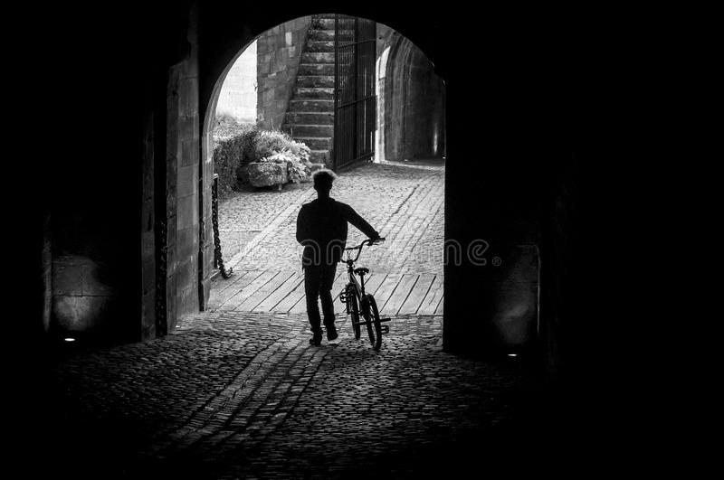 Cyclist silhouette crossing a dark tunnel stock image