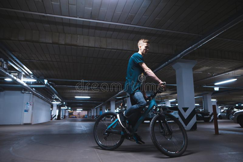 cyclist in an underground parking lot for cars. A man rides a bicycle by parking stock image