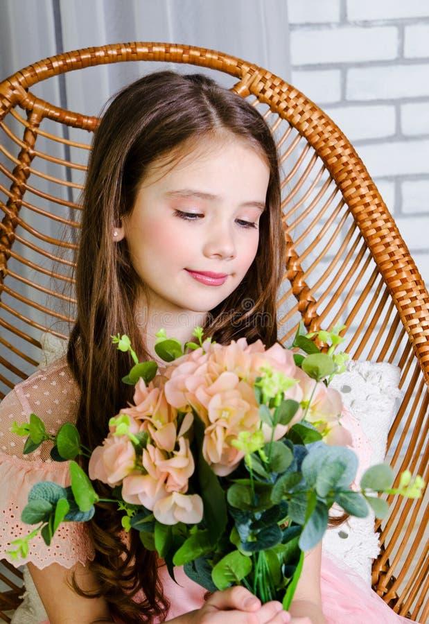 Portrait d'?coli?re de sourire adorable d'enfant de petite fille dans la robe de princesse se reposant dans la chaise images libres de droits
