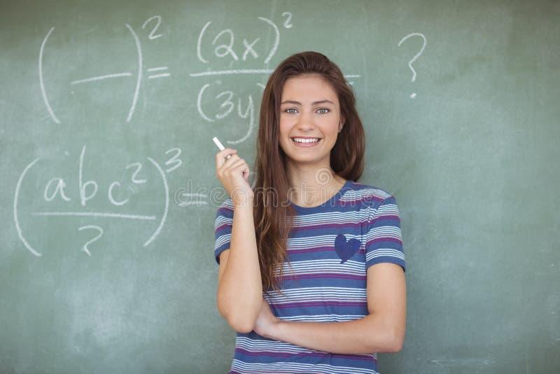 Portrait d'écolière feignant pour être un professeur dans la salle de classe photo stock