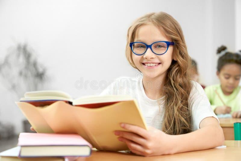 Portrait d'écolière se reposant et posant dans la salle de classe photo stock