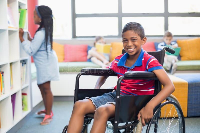 Portrait d'écolier handicapé sur le fauteuil roulant dans la bibliothèque photo stock