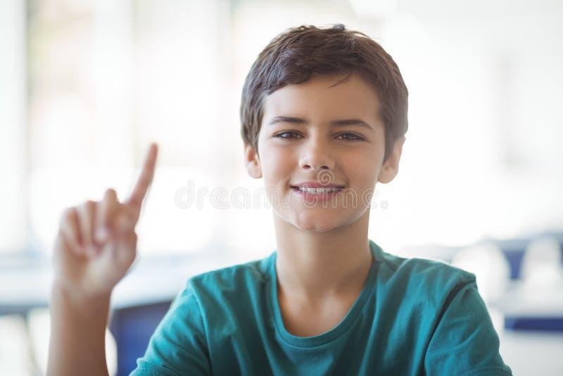Portrait d'écolier heureux soulevant la main dans la salle de classe images libres de droits