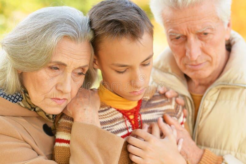 Portrait d'étreindre triste de grand-père, de grand-mère et de petit-fils photographie stock libre de droits