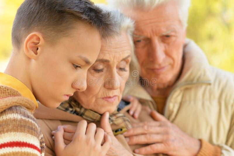 Portrait d'étreindre triste de grand-père, de grand-mère et de petit-fils photographie stock