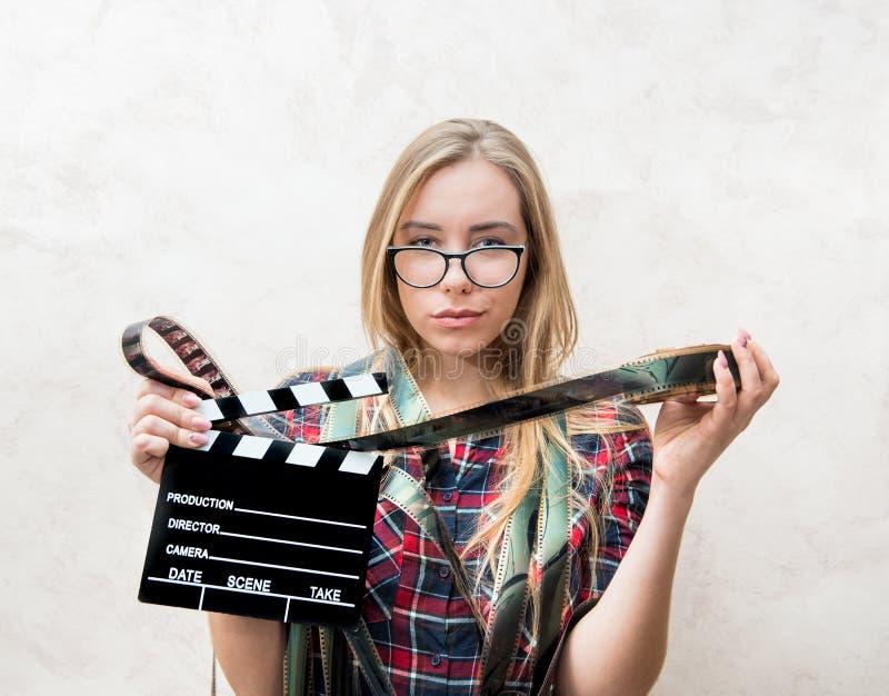 Portrait d'étudiant de film avec le panneau de film et de clapet photos libres de droits