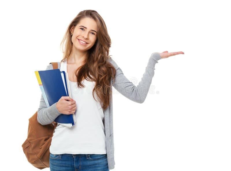 Portrait d'étudiant heureux montrant quelque chose d'isolement sur le Ba blanc photographie stock