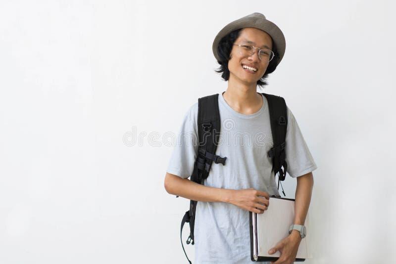 Portrait d'étudiant universitaire de sourire heureux avec le livre et de sac d'isolement sur le fond blanc photographie stock