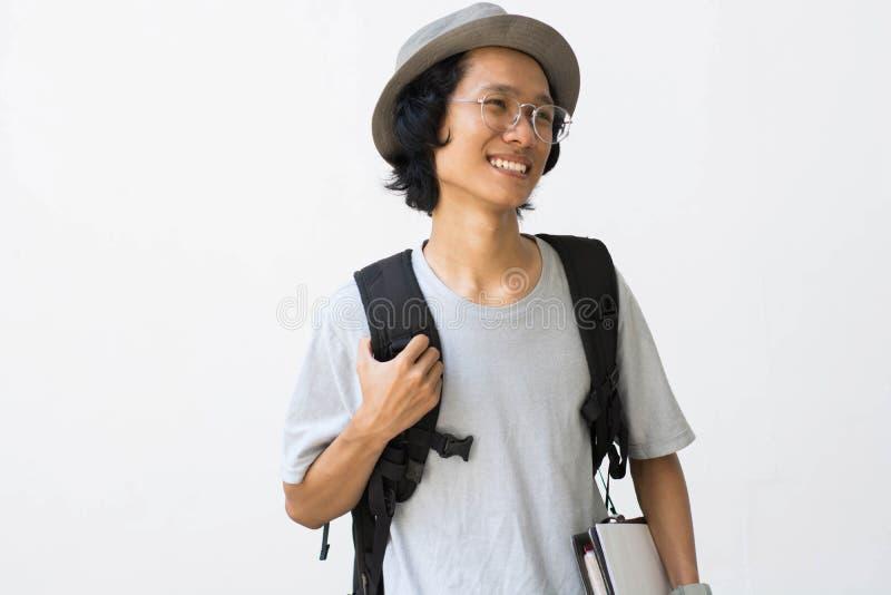 Portrait d'étudiant universitaire de sourire heureux avec le livre et de sac d'isolement sur le fond blanc photos stock