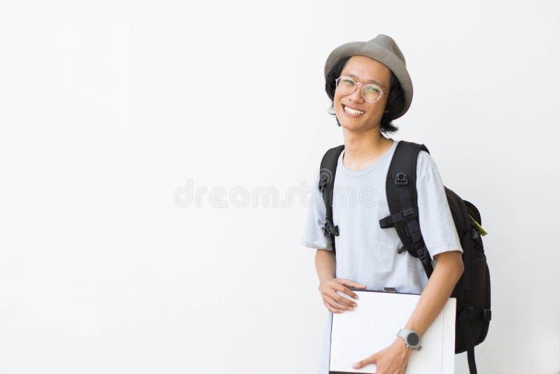 Portrait d'étudiant universitaire de sourire heureux avec le livre et de sac d'isolement sur le fond blanc images stock