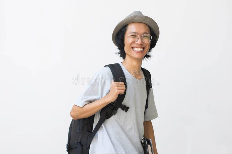 Portrait d'étudiant universitaire de sourire heureux avec le livre et de sac d'isolement sur le fond blanc photo stock