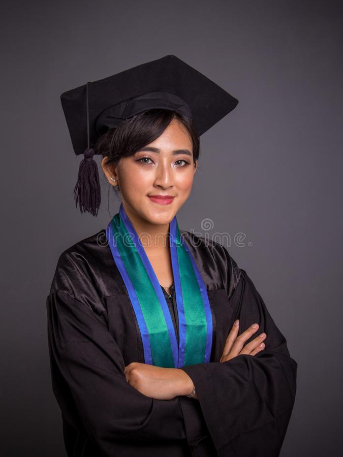 Portrait d'étudiante asiatique dans des équipements d'obtention du diplôme avec les bras croisés image libre de droits