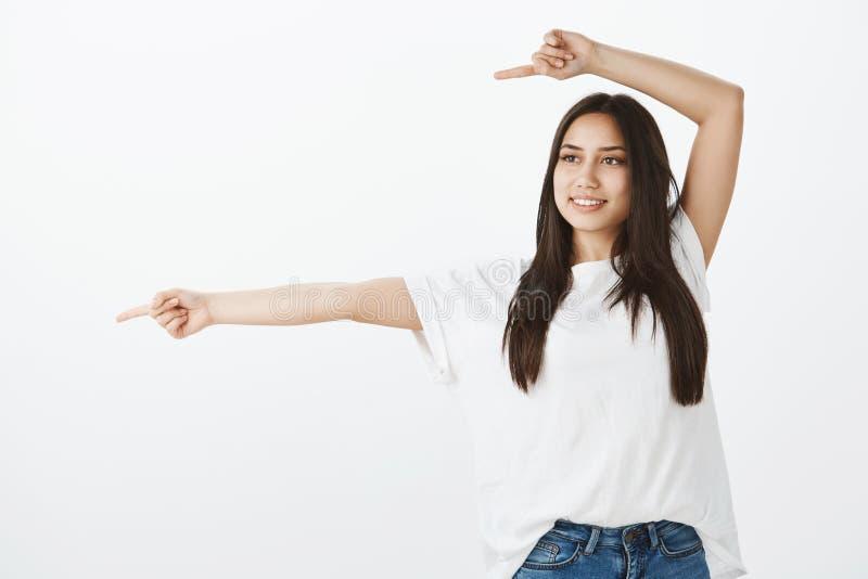 Portrait d'étudiante belle gaie dans le T-shirt blanc, soulevant le bras au-dessus de la tête et se dirigeant à gauche avec photo stock