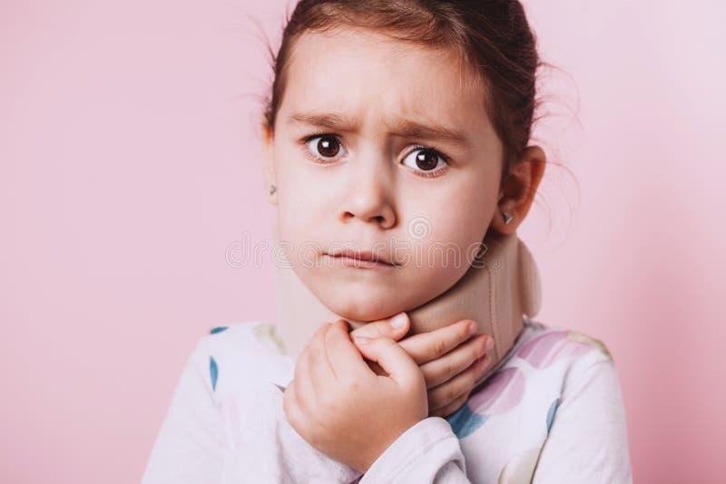 Portrait d'accolade de cou de port de petite fille sur le fond rose photo stock