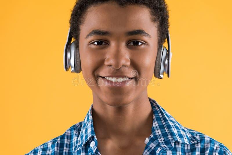 Portrait d'ado afro-américain heureux dans des écouteurs image libre de droits